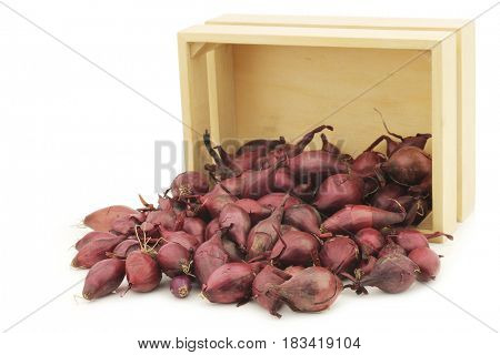 red seed onions in  a wooden box on a white background