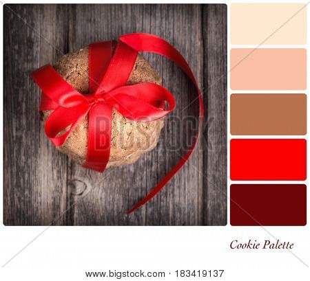 Homemade cookies tied with a red ribbon, over old wood background. In a colour palette with complimentary colour swatches.