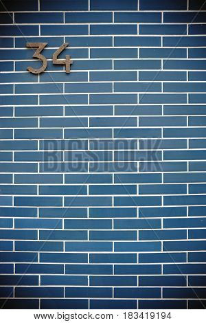 A nostalgic house number on a striking blue clinker brick wall.