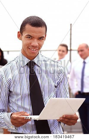 Holding a laptop, a young handsome black businessman is standing outside of a business building, confidently looking forward.