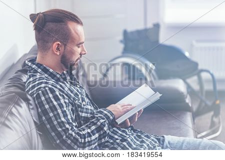 Interested in creative literature. Bearded smiling optimistic invalid sitting on the couch next to the wheelchair at home and relaxing while enjoying reading the book