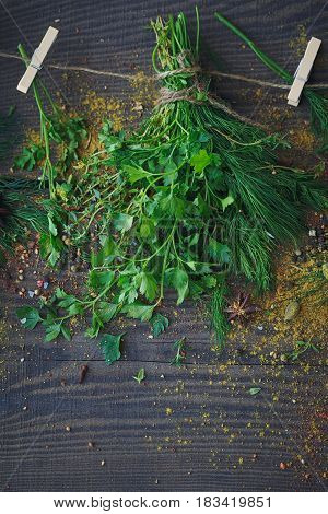 Mix of fresh herbs and spices assortment on wooden background. Fresh parsley thyme dill and mint leaves. Top view with copy space