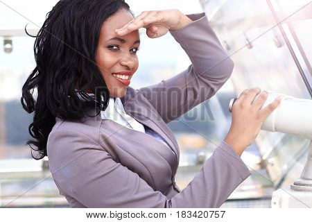 African woman looking through binoculars over the city
