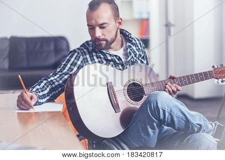Leading positive lifestyle. Bearded mature inspired disabled sitting on the wheelchair indoors and enjoying weekend while playing the guitar and writing song