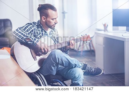 Involved in the process. Bearded skillful gifted disabled sitting on the wheelchair indoors and expressing positivity while playing the guitar