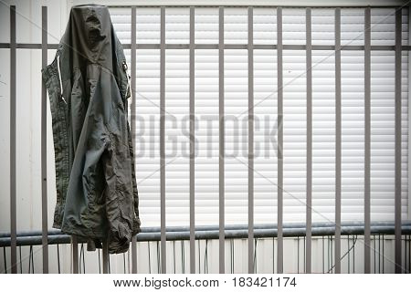 A raincoat hangs on a fence of a construction site.