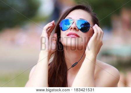 happy woman in blue glasses relaxing in the sun