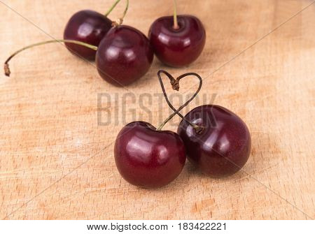 red cherries and heart on a wooden board