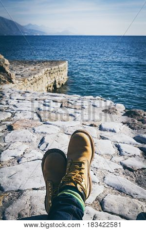 Ploce beach. Republic of Montenegro. Legs in yellow boots sea mountains and a puffy white clougs in the sky.