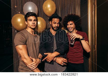 Portrait of three young men partying at the nightclub. Group of men having good times at pub.