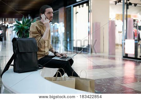 Young hipster guy call to a friend to tell about sales in shopping center. Walking in weekend in search of new clothes of modern collections. Blogger typing article of fashion shop.