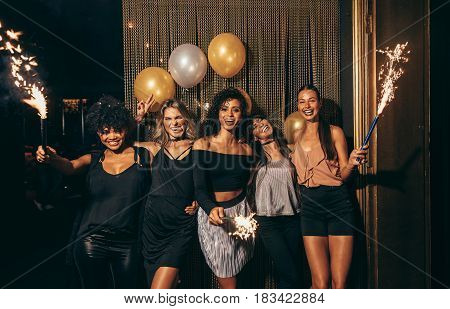 Shot of group of girls celebrating new years eve at the nightclub. Group of female friends partying in pub with sparklers.