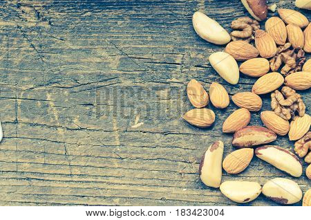 Concept - Nuts mix on old rustic wooden background with place for text. Almonds Brazil nuts and walnuts. Healthy edible seeds food ingredient on the table. Top view. Directly above. Copy space.