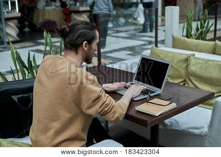 Young journalist working in open space in shopping center. Man typing message for a friends in the internet social network on mock up notebook. Back view on freelancer develop on new IT application