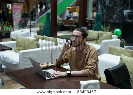 Yong creative person waiting for a customer in shopping center cafe and make phone conversation. Businessman planning weekend with friends and search entertainment in the internet. Holiday concept.