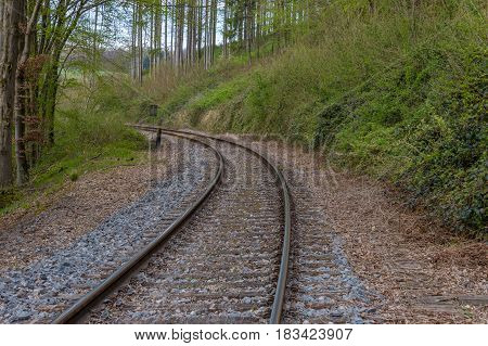 Train track in the middle of a european forest with stones dry weed trees and rusty iron