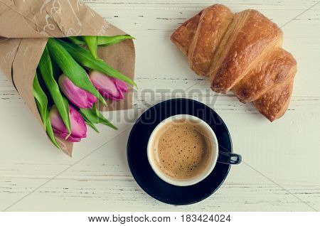 Cup of coffee with bouquet of pink tulips and croissant on white shabby chic background. Valentines Mothers Womens Day morning concept. Valentine's day breakfast. Top view. Copy space.