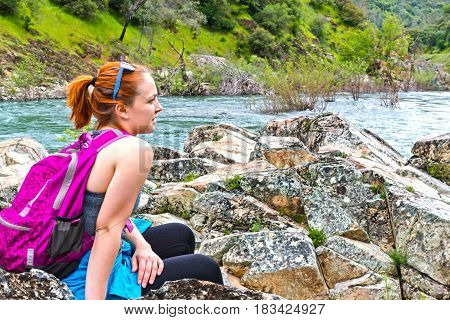 Young Girl Sitting on Rocks Near Fast River