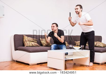 Buddies Watching Football Match On Tv At Home With Victory Screams