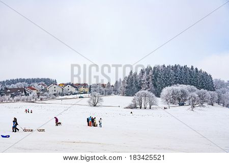 Hildren Are Skating At A Toboggan Run In Winter On Snow.