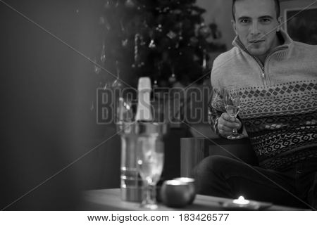 Portrait of a happy young man with a glass of champagne celebrating winter holidays at home beautifully decorated for Christmas