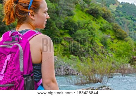 Young Girl Standing on Rocks Near Fast River