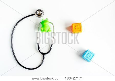 stethoscope, toys on children's doctor office white desk background top view mockup