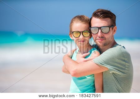 Happy father and his adorable little daughter at tropical beach having fun