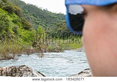 Young Girl With Glasses Looking Out Over River