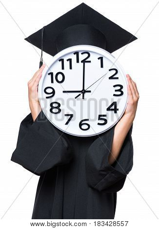 Portrait of a graduate girl or boy student in a black graduation gown with hat, holding big clock - isolated on white background. Child back to school, educational and time concept.