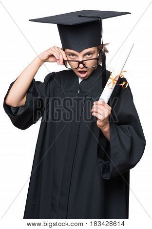 Portrait of a surprised graduate little girl student in a black graduation gown, hat and eyeglasses, holding diploma - isolated on white background. Educational concept.