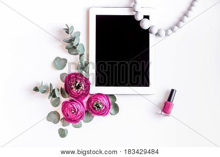 Modern spring design with bright pink flowers and tablet on white desk background top view moke up