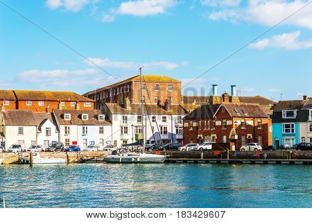 Boat anchored in a small harbor in the background stone buildings and promenade seaside tourist spot