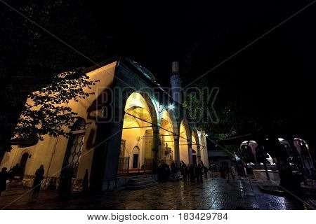SARAJEVO BOSNIA HERZEGOVINA - APRIL 15 2017: People praying in front of Gazi Husrev Begova mosque in Sarajevo. The mosque is one of the main landmarks of the ottoman part of the capital city of Bosnia