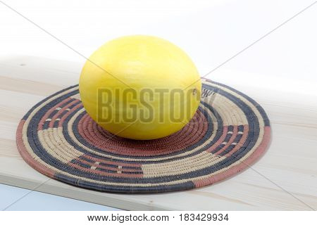 Canary Melon On A Spiral Bamboo Straw Rustic Placemat With Indigenous Style And Wood Board Isolated