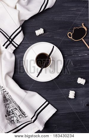 Black coffee in a white cup, vanilla bean, kitchen towel and marshmallow on a dark background. Top view