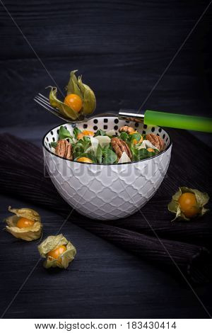 Homemade salad with physalis, parmesan and pecans on a dark wooden background