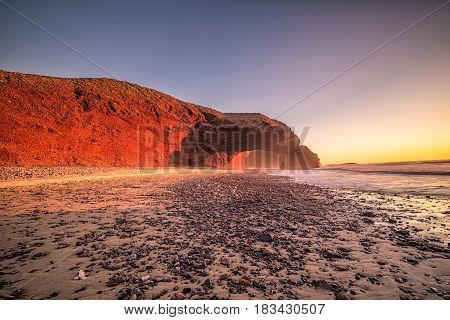 Sunset at red arches of Legzira beach, Sidi Ifni, Souss-Massa-Draa, Morocco.