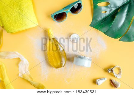 Sun protection cosmetic cream and lotion with beach outfit, sunglasses and cap on orange background top view