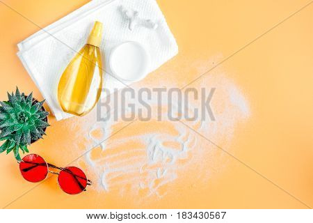 Woman cosmetic set with sun protection lotion and sunglasses for summer seaside rest on orange desk background top view mock-up