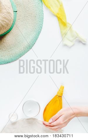 cream and lotion cosmetic for sun protection with hat in a sunbath concept on white background top view space for text