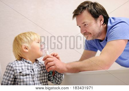 Middle Age Father Helping His Toddler Son With Inhalation Therapy By The Mask Of Inhaler
