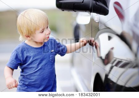 Little Boy Looking On His Reflection In Black Car