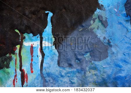 Textured abstract multicolor background. Close up. Dripping paint on rough,grunge plastered surface. Dirty old wall with different vivid colors : blue,black and red