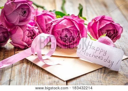 present design with Mother's day text and greeting-card and envelope on wooden desk background