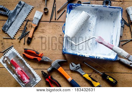 building decoration instruments with paint, roller, palette-knife in builder work on wooden background top view