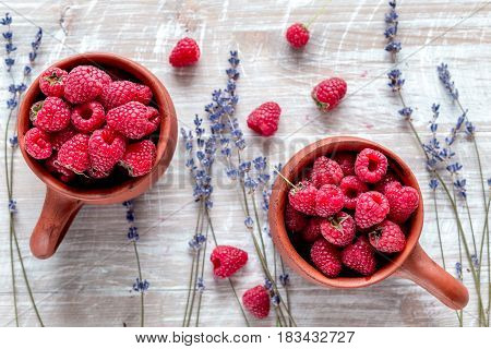 raspberry composition in pottery pots and cups and with dry lavender bouquet on rustic desk background top view
