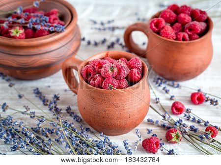 raspberry composition in pottery pots and cups and with dry lavender bouquet on rustic desk background