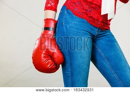 Unrecognizable woman wearing red boxing glove and tight blue jeans. Grey background.