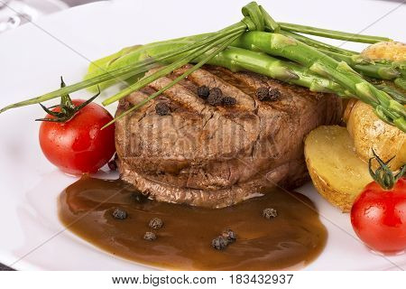 Close up on filet mignon with vegetables on the side